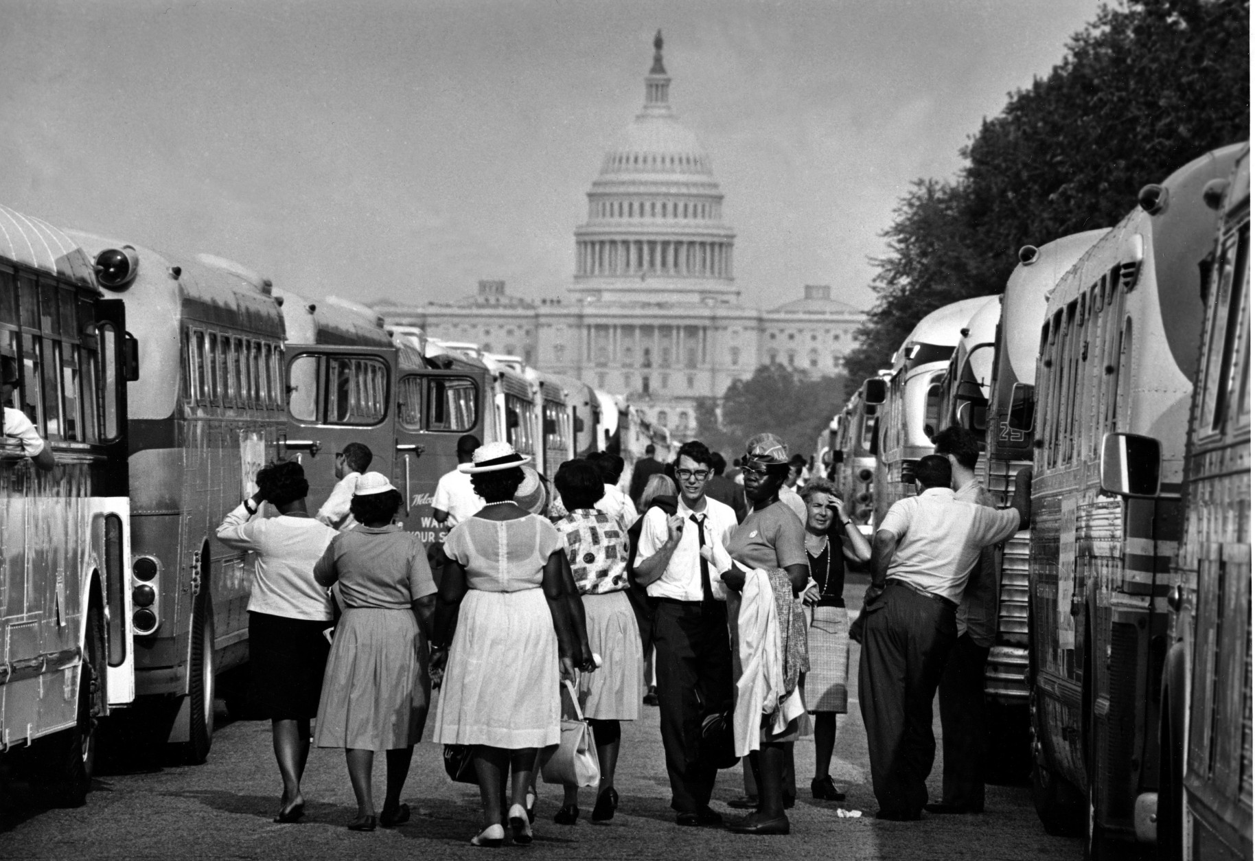 With the U.S. Capitol in the background, passengers for charter busses walk along a service roadway of the Mall in Washington, August 28, 1963, to find their transportation home after a civil rights demonstration estimated by police at more than 200,000 people.  (AP Photo)