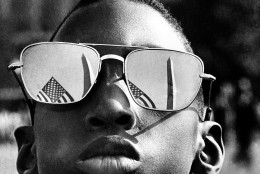 The top of the Washington Monument and part of a U.S. flag are reflected in the sunglasses of Austin Clinton Brown, 9, of Gainesville, Ga., as he poses at the Capitol where he joins others in the March on Washington, Aug. 28, 1963.  (AP Photo)