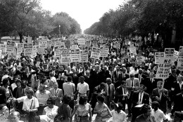 FILE - In this Aug. 28, 1963, file photo Dr. Martin Luther King Jr., center left with arms raised, marches along Constitution Avenue with other civil rights protestors carrying placards, from the Washington Monument to the Lincoln Memorial during the March on Washington. Next Wednesday, the nation's first black president, Barack Obama, will stand near the spot where Martin Luther King Jr. stood 50 years ago, a living symbol of the racial progress King dreamed about, and enunciate where he believes this nation should be headed. (AP Photo, File)