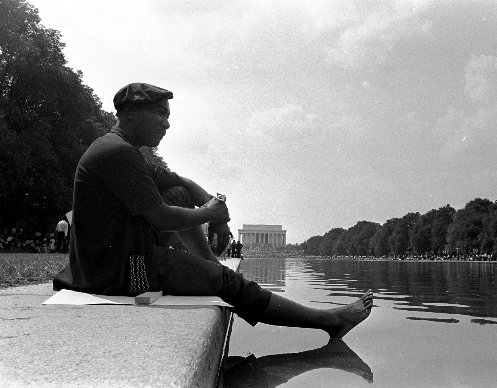 Sitting on his placard with his shoes off, a civil rights marcher cooling off his  bare foot on the  surface of the reflecting pool near the Lincoln memorial following the March on Washington, August 28, 1963.  (AP Photo)