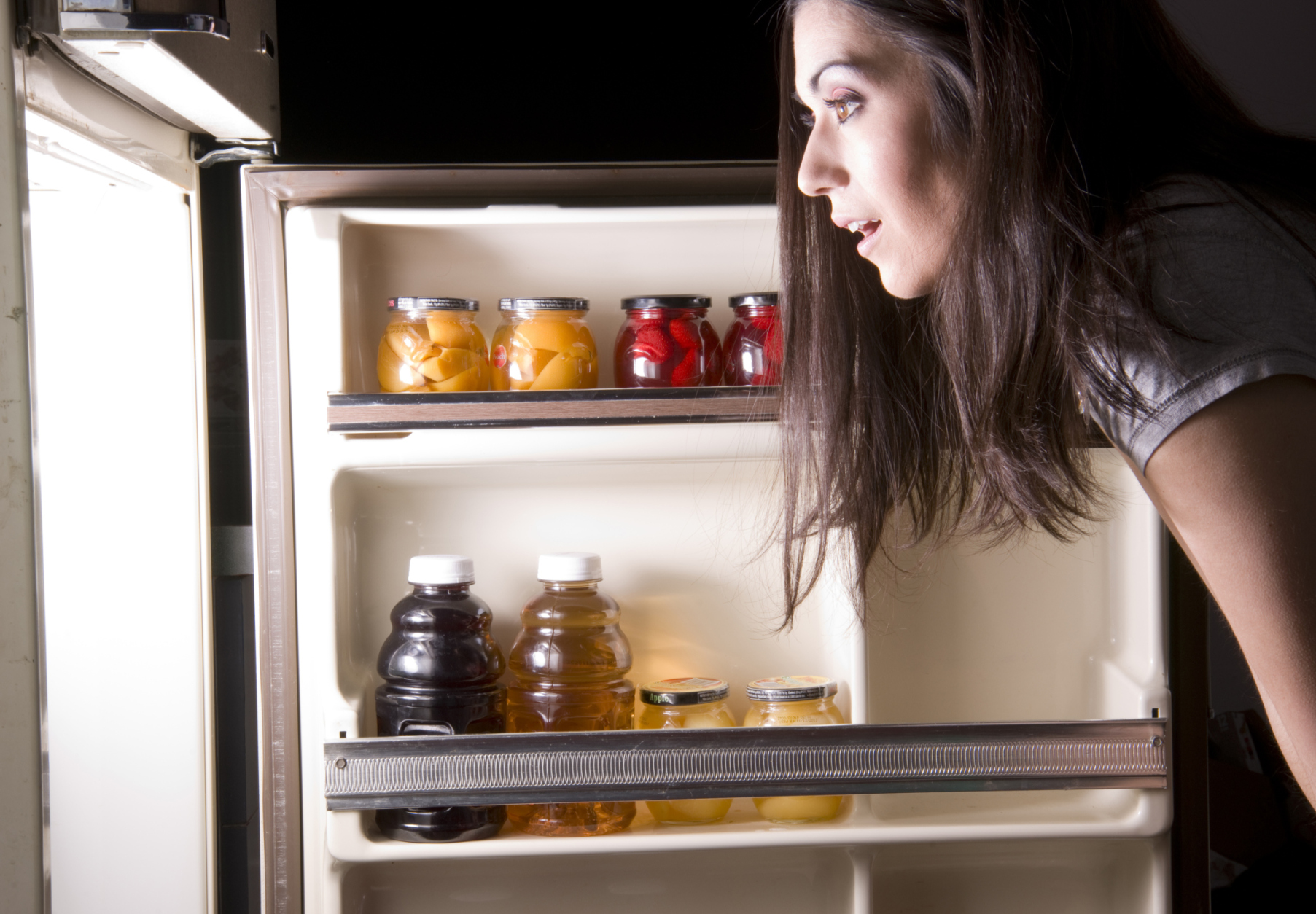 woman looking into the fridge looking for food