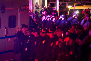 Mourners stand at attention as the bodies of two fallen NYPD police officers are transported from Woodhull Medical Center, Saturday. (AP Photo/John Minchillo)
