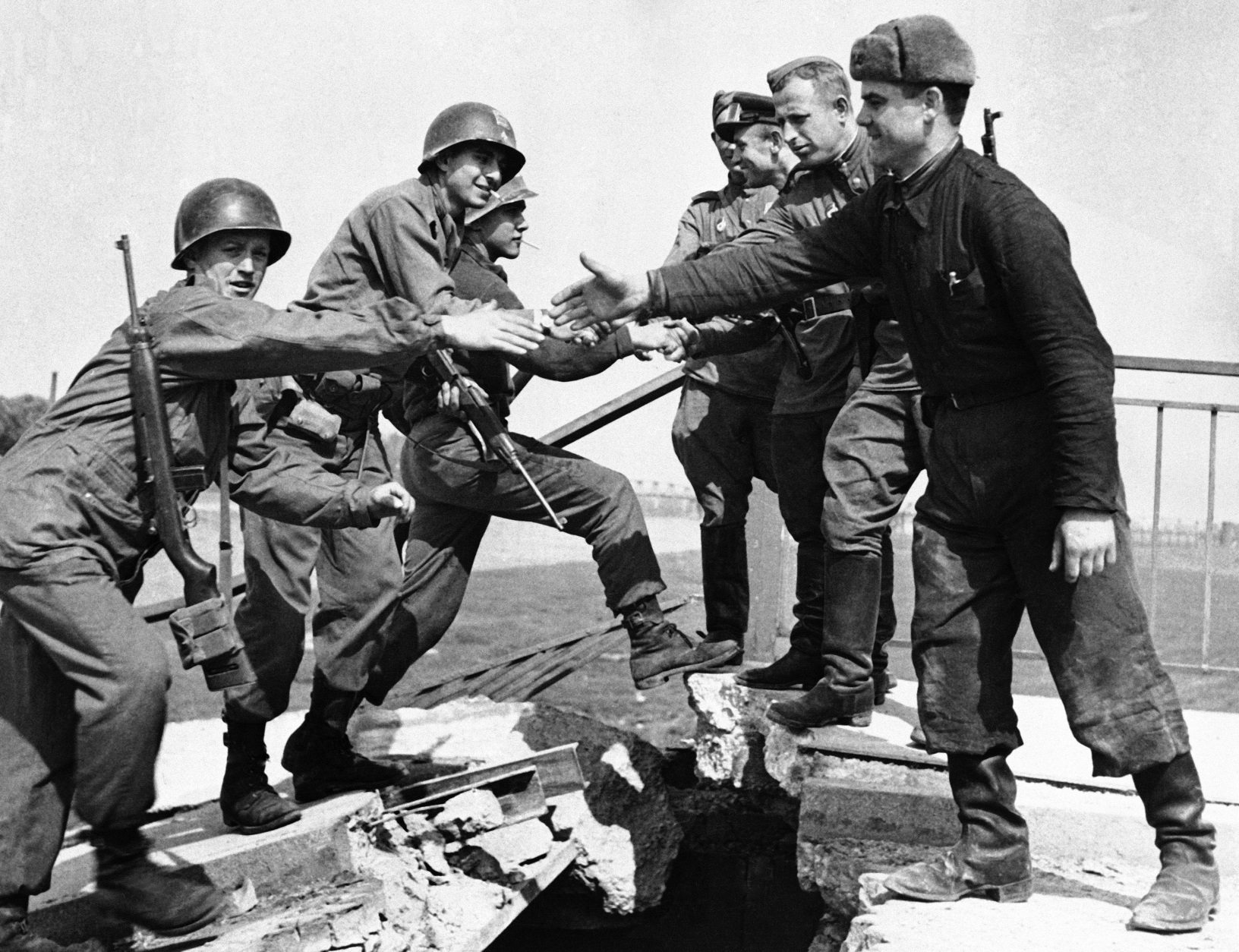 FILE - In this April 26, 1945, file photo, U.S. and Russian troops meet on the wrecked bridge over the Elbe River at Torgau, Germany. The Americans, left, and Russian soldiers are shown as they reach out to grasp each other's hands. The picture is part of an exhibition in Berlin marking the 70th anniversary of the end of World War II. (AP Photo)