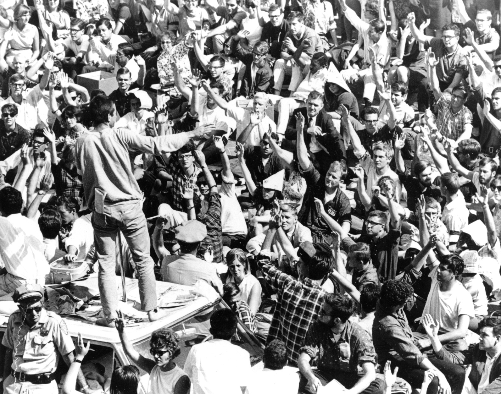 FILE - In this Oct. 2, 1964 file photo, standing atop the crushed roof of a campus police car, a University of California student asks Cal students to identify themselves during third day of Free Speech Movement demonstrations in Berkeley, Calif. One student has been arrested and confined in the police car which is surrounded by the demonstrators. The fall of 2014 marks the 50th anniversary of the Free Speech Movement, a protest that only lasted for three months but set the stage for the turbulent 1960s. (AP Photo, File)