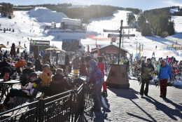 In this Dec. 11, 2014 photo, skiers and snowboarders eat lunch in the sun at the base of Breckenridge, in the Colorado Rocky Mountains. Business is booming in Colorado's mountain resorts, and the addition of recreational marijuana stores this year has attracted droves of customers curious about legalized pot. But in some quarters, there's anxiety that ski towns have embraced marijuana a little too much. (AP Photo/Brennan Linsley)