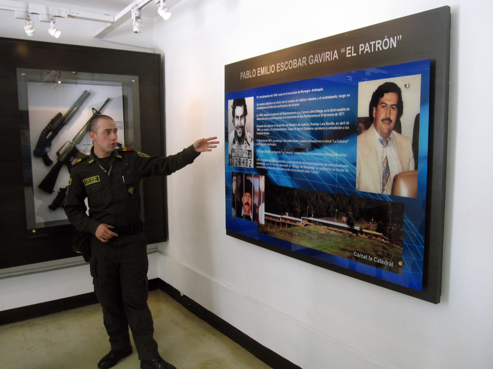 This Dec. 31, 2013 photo shows Kevin Riano explaining an exhibit about Pablo Escobar at the National Police Museum in Bogota, Colombia. Escobar, the notorious drug kingpin, was assassinated in a police ambush in Medellin in 1993. The museum offers free tours in English led by young Colombians like Riano who are fulfilling a required national service stint. (AP Photo/Beth J. Harpaz)