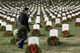 A unidentified woman walks with a holiday wreaths during Wreaths Across America's 150th anniversary, Saturday, Dec. 13, 2014, at Arlington National Cemetery in Arlington, Va. (AP Photo/Luis M. Alvarez)
