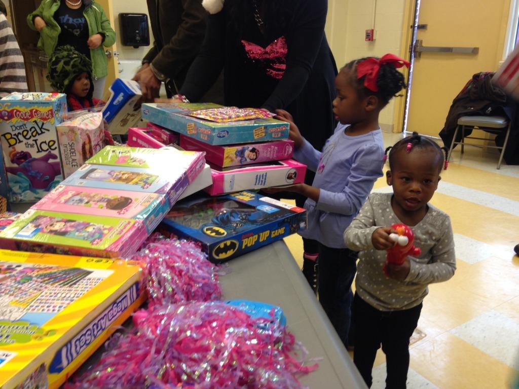 Kids receive gifts in Ward 8. (WTOP/Megan Cloherty)