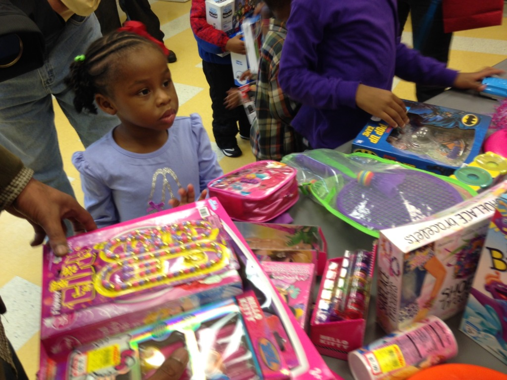 A little girl looks at a table of donated gifts. (WTOP/Megan Cloherty)