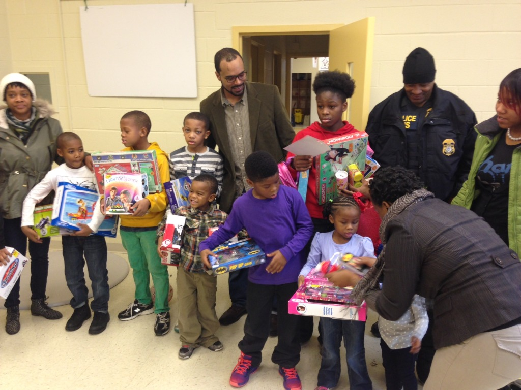 Children pose with their gifts in Ward 8 (WTOP/Megan Cloherty)