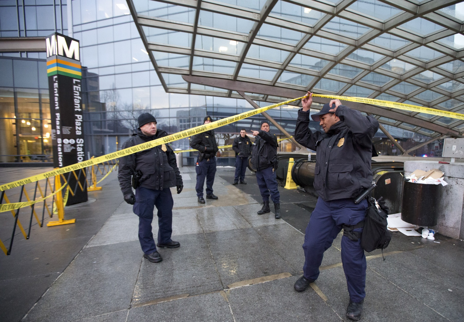Officers secure the entrance to L'Enfant Plaza Station in Washington, Monday, Jan. 12, 2015, following an evacuation. Metro officials say one of the busiest stations in downtown Washington has been evacuated because of smoke. Authorities say the source of the smoke is unknown. (AP Photo/Manuel Balce Ceneta)