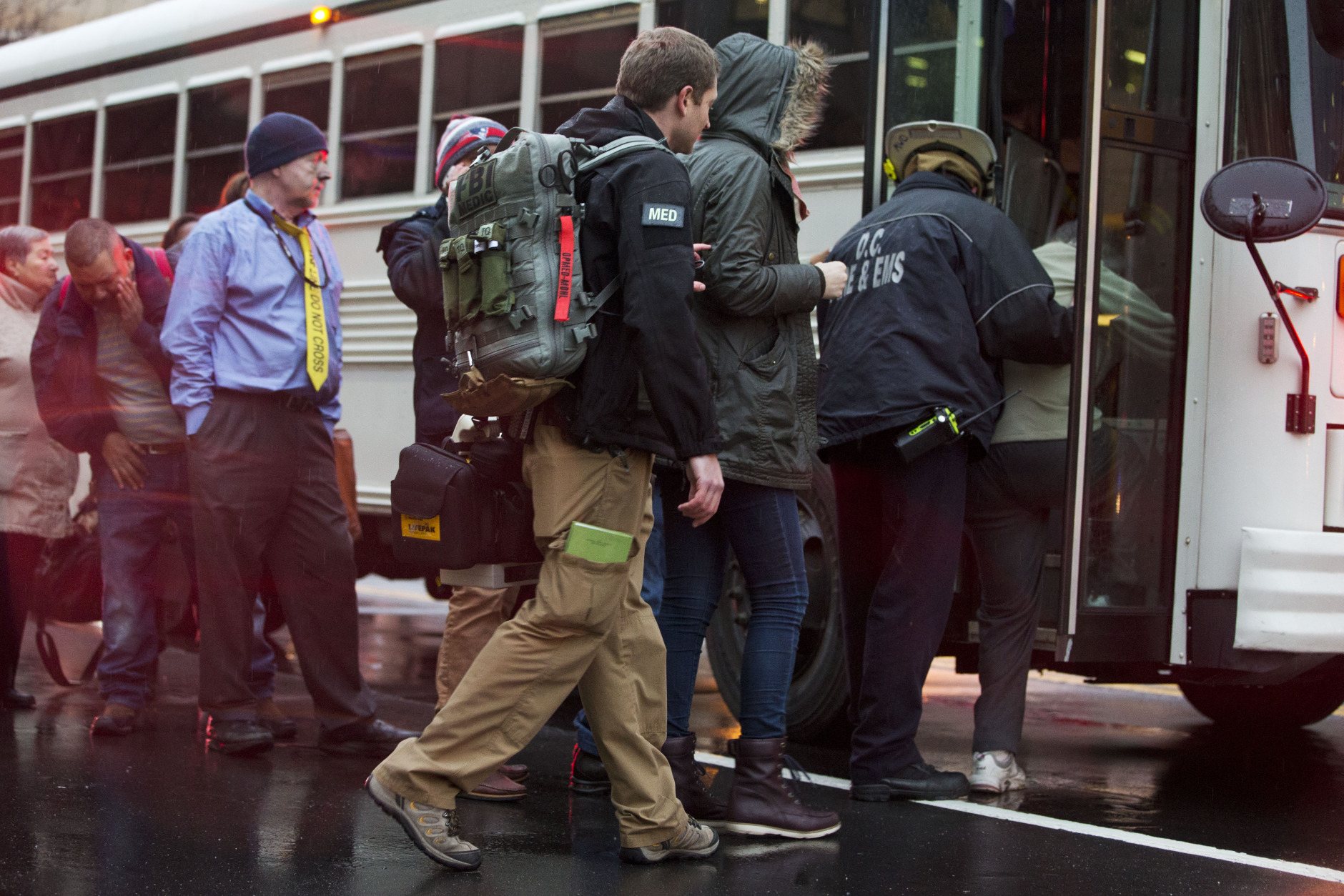 An FBI Medic, center, helps people onto a bus after they were evacuated from a smoke filled Metro subway tunnel in Washington, Monday, Jan. 12, 2015. Metro officials say one of the busiest stations in downtown Washington has been evacuated because of smoke.  Authorities say the source of the smoke is unknown.   (AP Photo/Jacquelyn Martin)