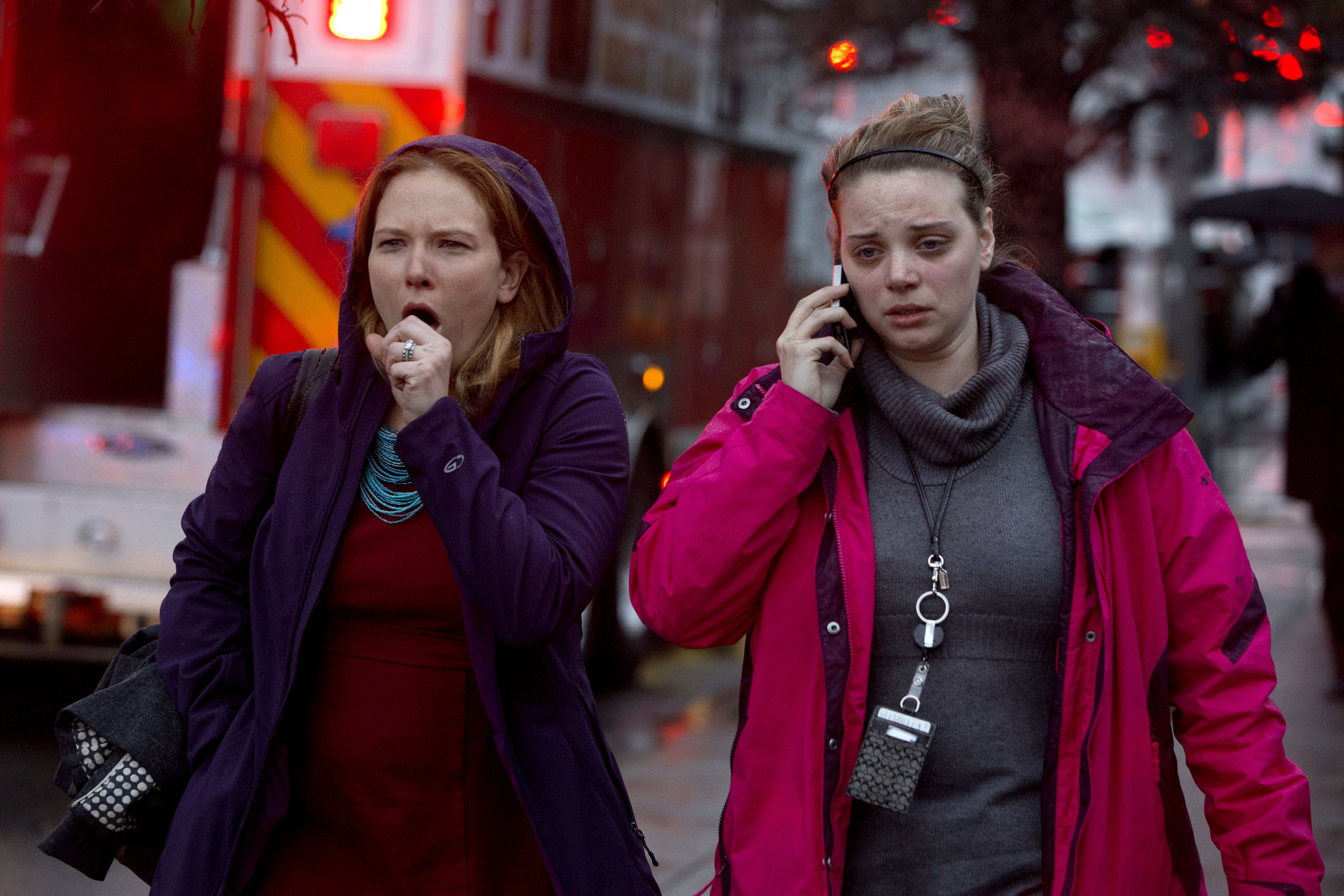 A woman coughs hard as she and another woman walk past an evacuation of people from a smoke filled Metro subway tunnel in Washington, Monday, Jan. 12, 2015. Metro officials say one of the busiest stations in downtown Washington has been evacuated because of smoke.  Authorities say the source of the smoke is unknown.   (AP Photo/Jacquelyn Martin)