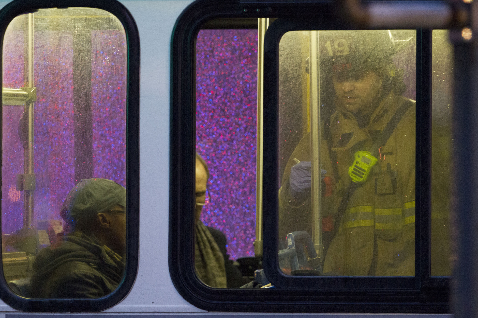 A firefighter attends people on a bus to assess triage needs after people were evacuated from a smoke filled Metro subway tunnel in Washington, Monday, Jan. 12, 2015. Metro officials say one of the busiest stations in downtown Washington has been evacuated because of smoke.  Authorities say the source of the smoke is unknown.  (AP Photo/Jacquelyn Martin)