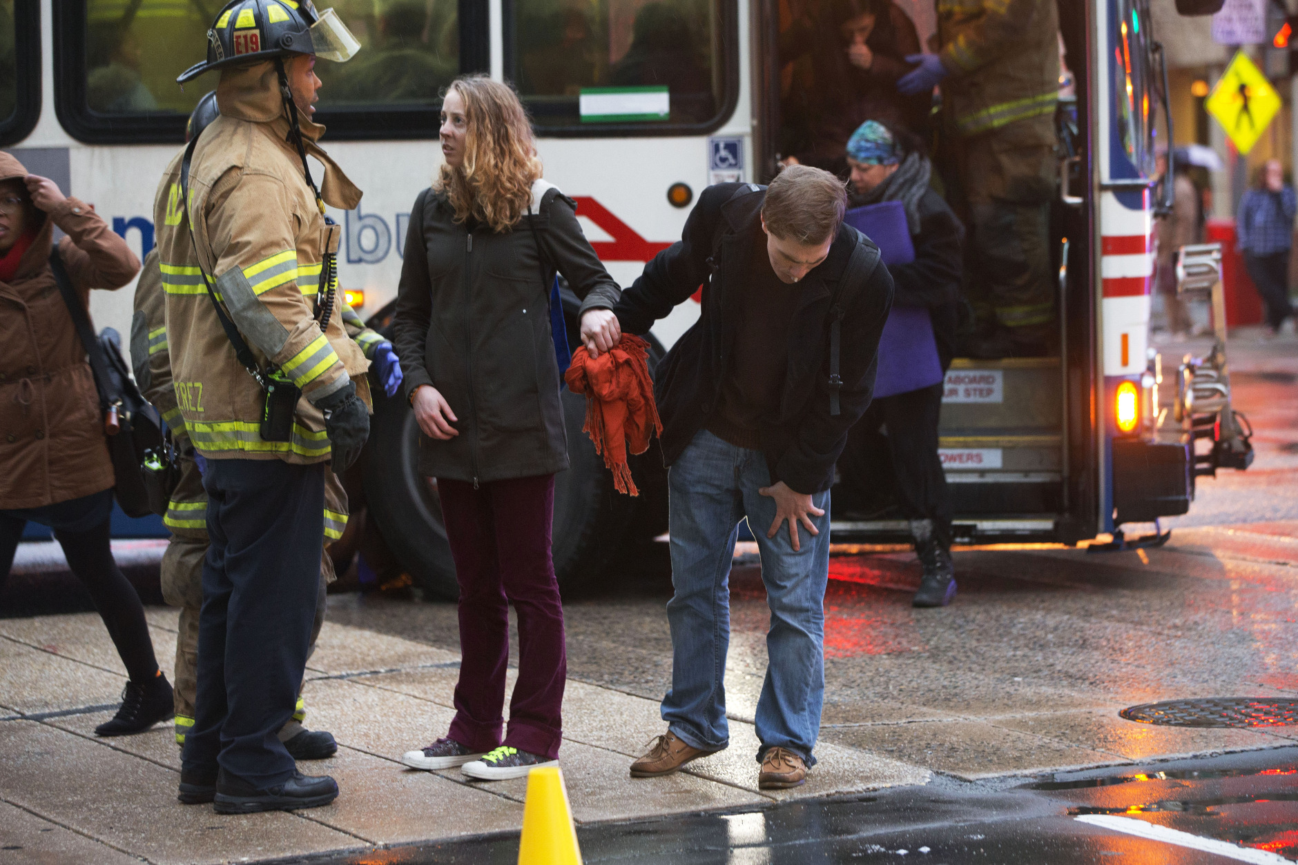 A couple holds hands as the man coughs while speaking with a firefighter after people were evacuated from a smoke filled Metro subway tunnel in Washington, Monday, Jan. 12, 2015. Metro officials say one of the busiest stations in downtown Washington has been evacuated because of smoke.  Authorities say the source of the smoke is unknown.   (AP Photo/Jacquelyn Martin)