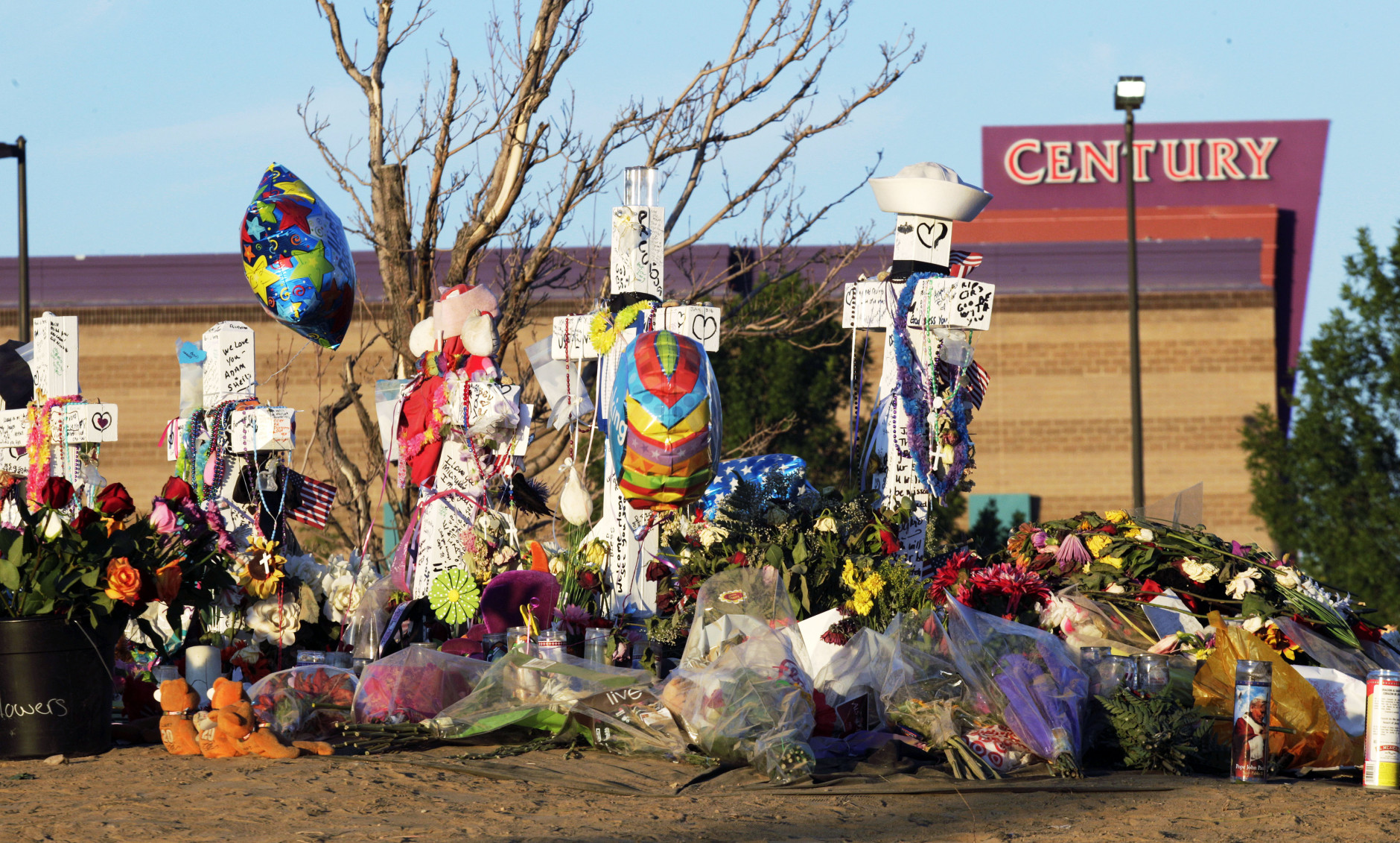 """FILE - In this July 27, 2012 file photo, crosses, flowers and other mementos of the victims of the Aurora, Colo. movie theater shooting are shown at sunrise with the movie theater in the background. Jury selection begins Tuesday, Jan. 20, 2015, in the trial of accused gunman James Holmes in the shootings at the Denver-area movie theater showing """"The Dark Knight Rises"""" that left 12 dead and 70 wounded. Prosecutors are seeking the death penalty. Holmes pleaded not guilty by reason of insanity. His attorneys have acknowledged he was the gunman but say he is mentally ill and was gripped by a psychotic episode when he opened fire in the theater. (AP Photo/Ted S. Warren, File)"""