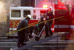 FILE - In this Jan. 12, 2015 file photo, a woman is transported in a wheelchair onto an ambulance as people are evacuated from a smoke filled Metro subway tunnel in Washington. Passengers on a smoke-filled subway train in the nation's capital were still asking when help would arrive 27 minutes after the smoke was first reported, District of Columbia officials said Thursday. One woman died and dozens more were sickened when the train filled with smoke Monday afternoon near a busy station in downtown Washington. The cause of the electrical malfunction that led to the smoke remains under investigation. (AP Photo/Jacquelyn Martin, File)