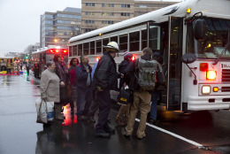 Coughing people are taken onto a bus as they are evacuated from a smoke filled Metro subway tunnel in Washington, Monday, Jan. 12, 2015. Metro officials say one of the busiest stations in downtown Washington has been evacuated because of smoke.  Authorities say the source of the smoke is unknown.  (AP Photo/Jacquelyn Martin)