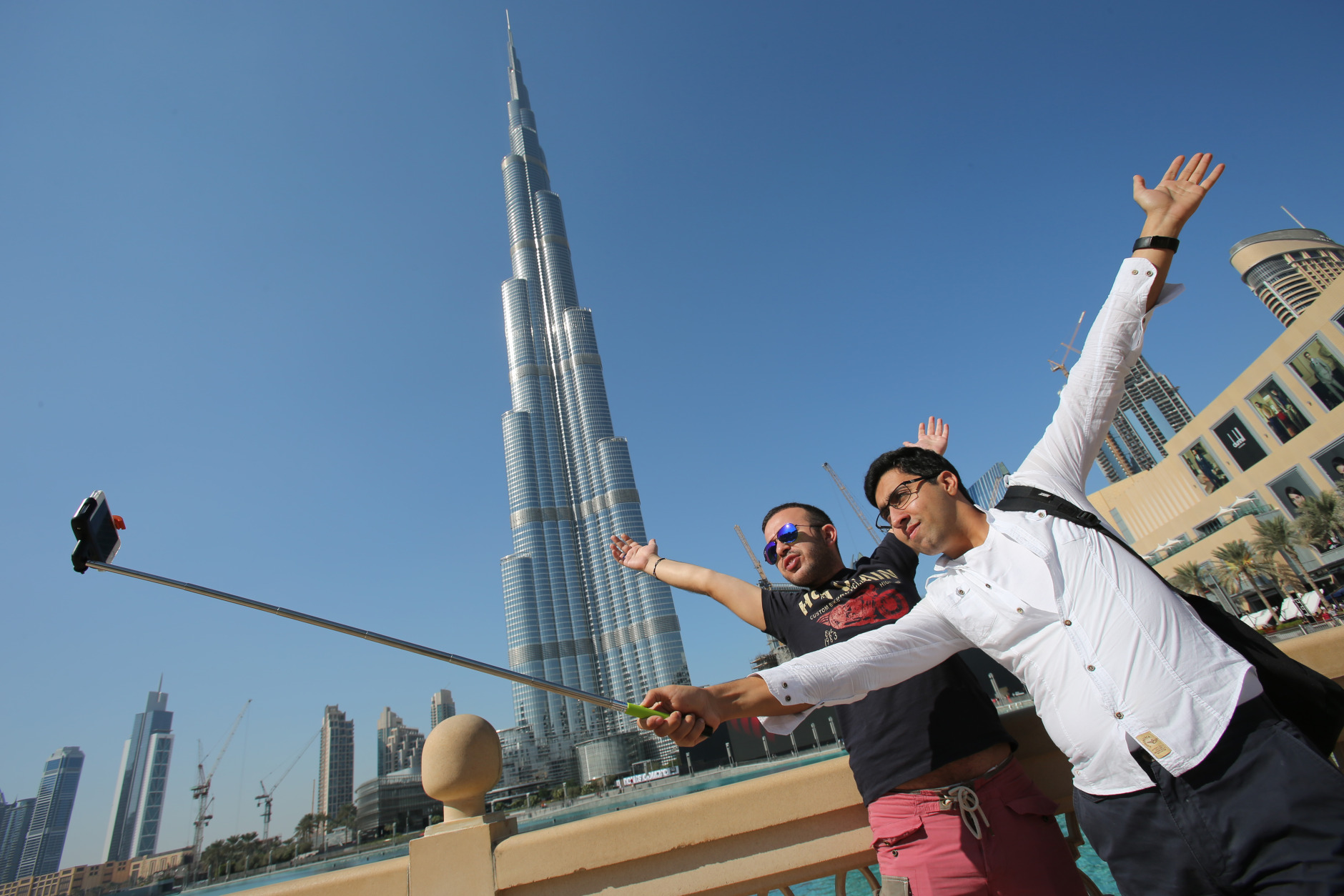 "In this Tuesday, Jan. 6, 2015 photo, Rasul Alekberov holds a selfie stick next to his friend Gudrat Aghayev both tourists from Republic of Azerbaijan while they take a selfie in front of ""Burj Khalifa"", world's tallest tower in Dubai, United Arab Emirates. Selfie sticks have become popular among tourists because you don't have to ask strangers to take your picture, and you can capture a wide view in a selfie without showing your arm. (AP Photo/Kamran Jebreili)"