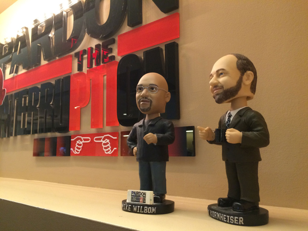 Bobbleheads of the hosts stand in front of the logo in PTI's D.C. offices. (WTOP/Noah Frank)