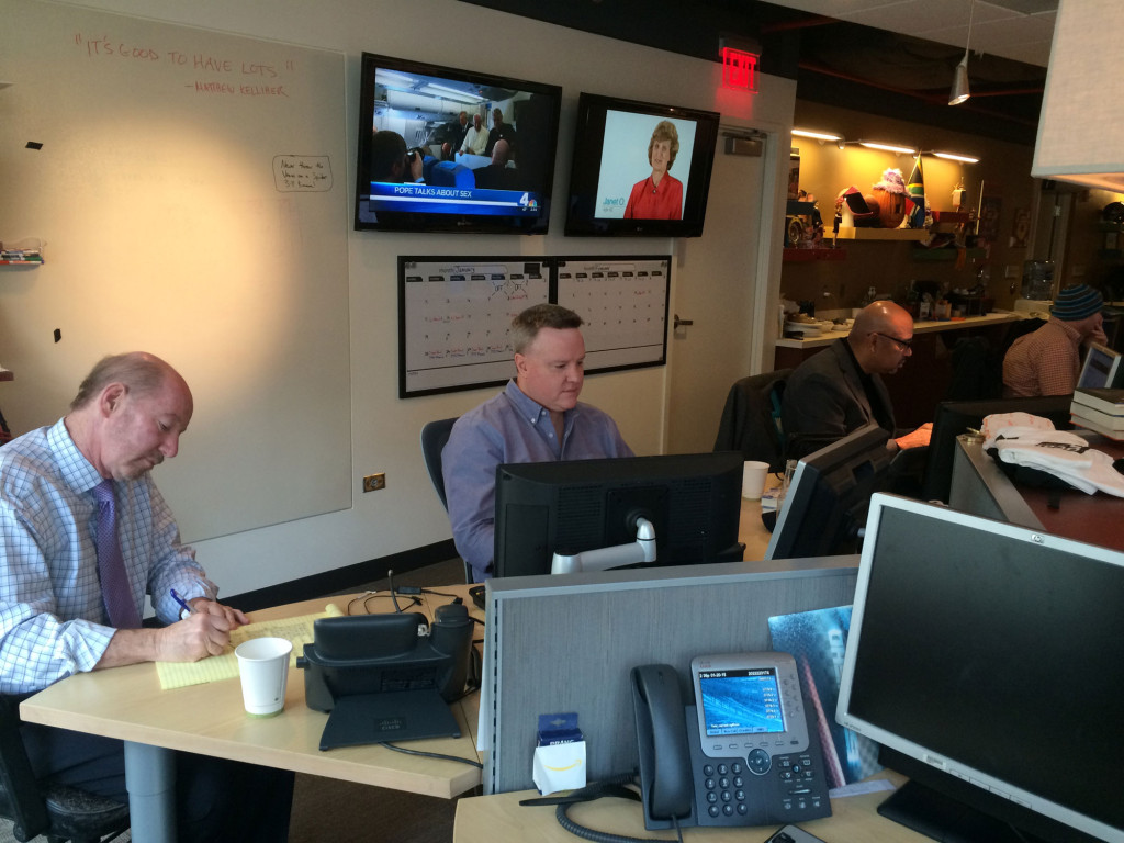 (From left) Kornheiser, Kelliher and Wilbon run through the day's topics prior to taping. (WTOP/Noah Frank)