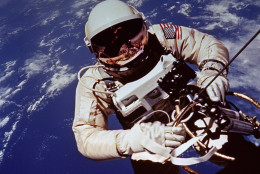 In this file photo, astronaut Ed White moves away from his Gemini 4 capsule as his golden tether unreels from a black bag in which it was kept until he emerged from the spacecraft.  He somersaulted away from most of the tether's length, then maneuvered back with the aid of an oxygen rocket gun.  This picture was made by White's fellow astronaut, James McDivitt, June 8, 1967, with a Hasselblad camera. (AP Photo/NASA)