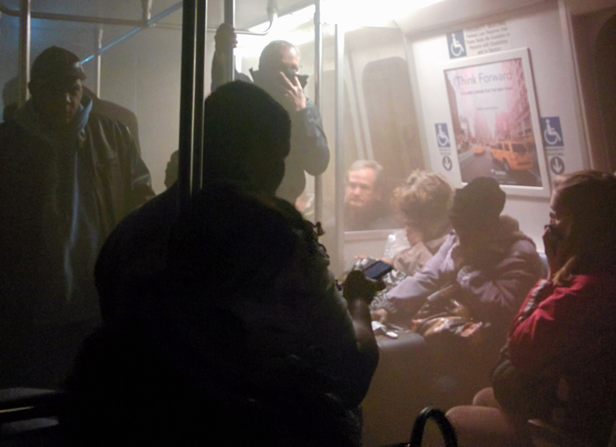 Smoke fills a Washington Metro system subway car near the L'Enfant Plaza station in Washington, Monday, Jan. 12, 2015. An electrical malfunction that filled the busy subway station with smoke killed one woman and sent dozens of people to hospitals. (AP Photo/Andrew Litwin)