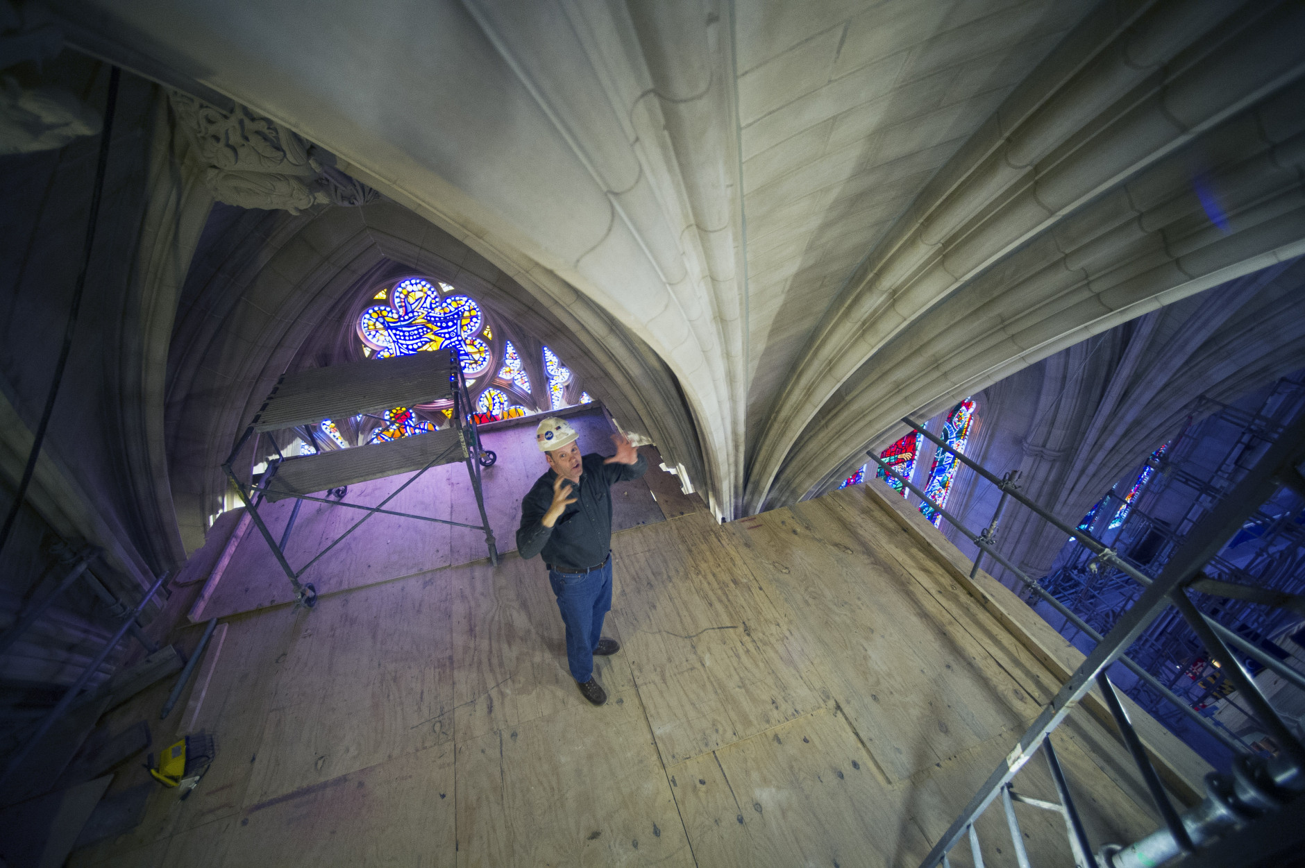 Head Mason Joe Alonso talks about repairs and cleaning of the stonework in the ceiling at the Washington National Cathedral on scaffolding 65 feet above the nave floor, Wednesday, Feb. 18, 2015, in Washington. The Washington National Cathedral has finished the first phase of restoration work needed after an earthquake in 2011. The iconic Episcopal cathedral in northwest Washington is holding a news conference Wednesday to discuss details of the restoration work, estimated to cost $32 million overall. Additional restoration work is expected to take years. (AP Photo/Cliff Owen)