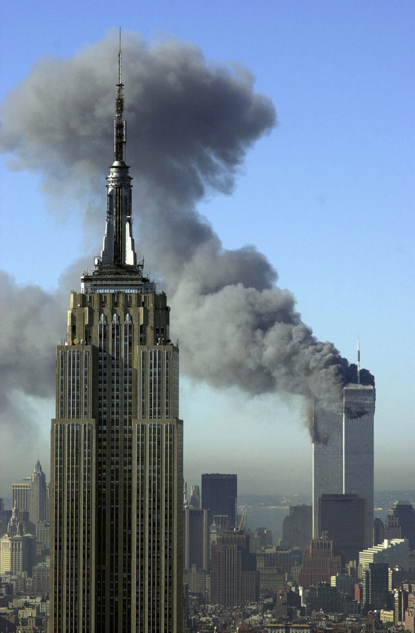 FILE - In this Tuesday, Sept. 11, 2001 file photo, plumes of smoke rise from the World Trade Center buildings in New York. The Empire State building is seen in the foreground. For years, a handful of current and former American officials have been urging President Barrack Obama to release secret files that they believe document links between the government of Saudi Arabia and the terrorist attacks of September 11, 2001. Other officials, including the executive director of the 9-11 commission, have said the classified documents don't prove that the Saudi government knew about or financed the attacks_and that making them public would fuel bogus conspiracy theories. (AP Photo/Patrick Sison, File)