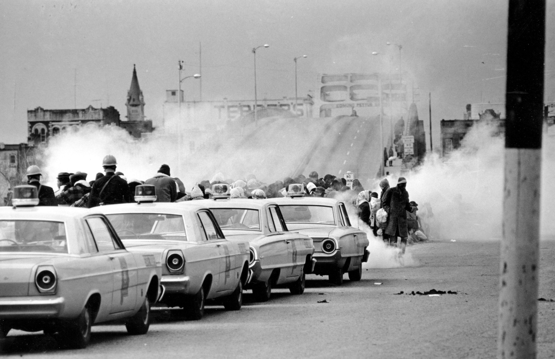 """FILE - In this March 7, 1965 file photo, clouds of tear gas fill the air as state troopers, ordered by Gov. George Wallace, break up a demonstration march in Selma, Ala., on what became known as """"Bloody Sunday."""" The incident is widely credited for galvanizing the nation's leaders and ultimately yielded passage of the Voting Rights Act of 1965. (AP Photo/File)"""