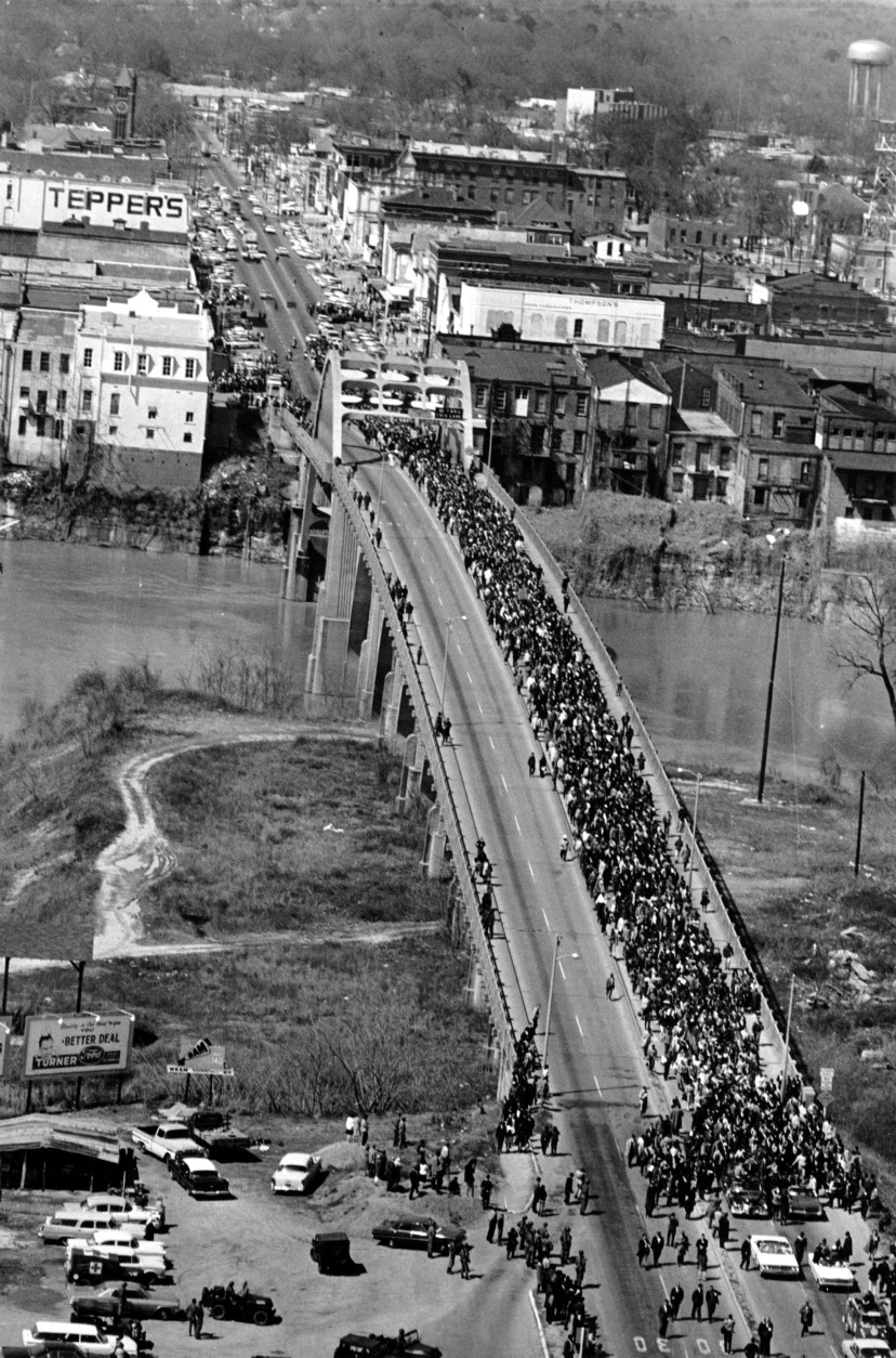 FILE - In this March 21, 1965 file photo, civil rights marchers cross the Alabama river on the Edmund Pettus Bridge in Selma, Ala. to the State Capitol of Montgomery. The Edmund Pettus Bridge gained instant immortality as a civil rights landmark when white police beat demonstrators marching for black voting rights 50 years ago this week in Selma, Alabama. What's less known is that the bridge is named for a reputed leader of the early Ku Klux Klan. Now, a student group wants to rename the bridge that will be the backdrop when President Barack Obama visits Selma on March 7, 2015.  (AP Photo/File)