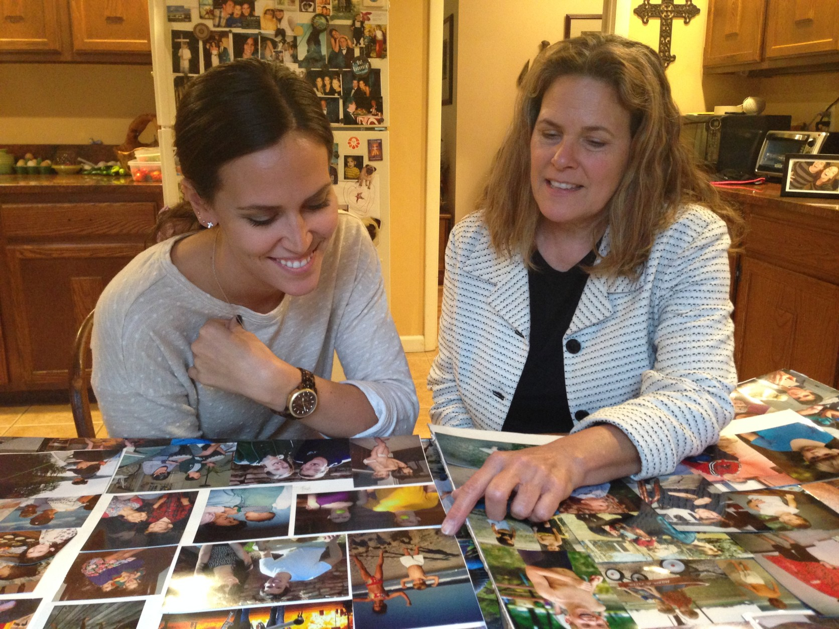Ginny and Anne Atwood look at pictures of Christopher that they arranged on a poster board for his funeral. (WTOP/Jamie Forzato)