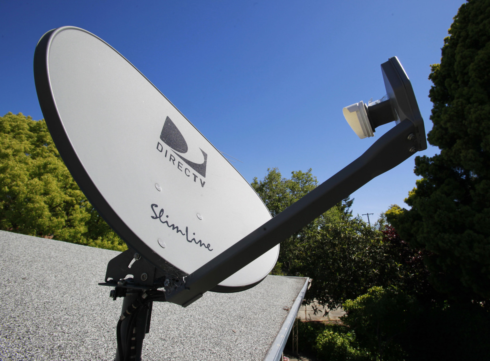 FILE - In this May 6, 2010 file photo, a DirecTV satellite dish is attached to a roof at a home in Palo Alto, Calif. The government is taking the nation's biggest satellite TV provider to court, accusing DirecTV of misleading millions of consumers about the cost of its programming. The Federal Trade Commission said Wednesday that its complaint charges DirecTV Inc. with deceptively advertising a discounted 12-month programming package. Consumers weren't clearly told that the package requires a two-year contract, the commission said.  (AP Photo/Paul Sakuma, File)