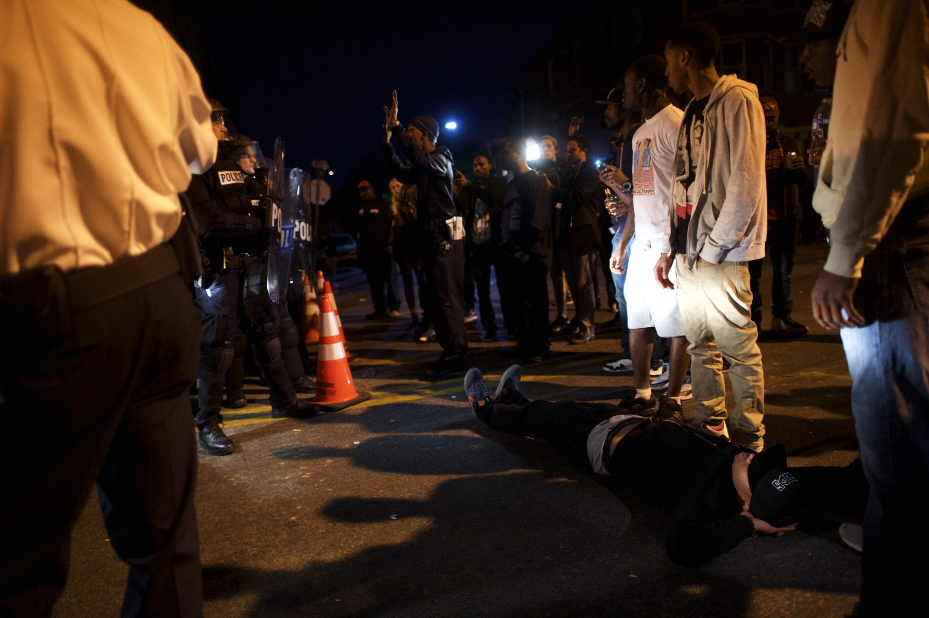BALTIMORE, MD - APRIL 28:  A protestor lies in front of a police barricade blocking the exit of a vehicle the night after citywide riots over the death of Freddie Gray on April 28, 2015 in Baltimore, Maryland. Freddie Gray, 25, was arrested for possessing a switch blade knife April 12 outside the Gilmor Houses housing project on Baltimore's west side. According to his attorney, Gray died a week later in the hospital from a severe spinal cord injury he received while in police custody. (Photo by Mark Makela/Getty Images)