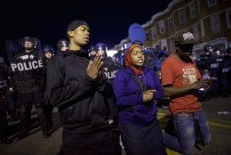 Protestors say the Lord's Prayer beside riot police the night after citywide riots over the death of Freddie Gray on April 28, 2015 in Baltimore, Maryland. Freddie Gray, 25, was arrested for possessing a switch blade knife April 12 outside the Gilmor Houses housing project on Baltimore's west side. According to his attorney, Gray died a week later in the hospital from a severe spinal cord injury he received while in police custody. (Photo by Mark Makela/Getty Images)