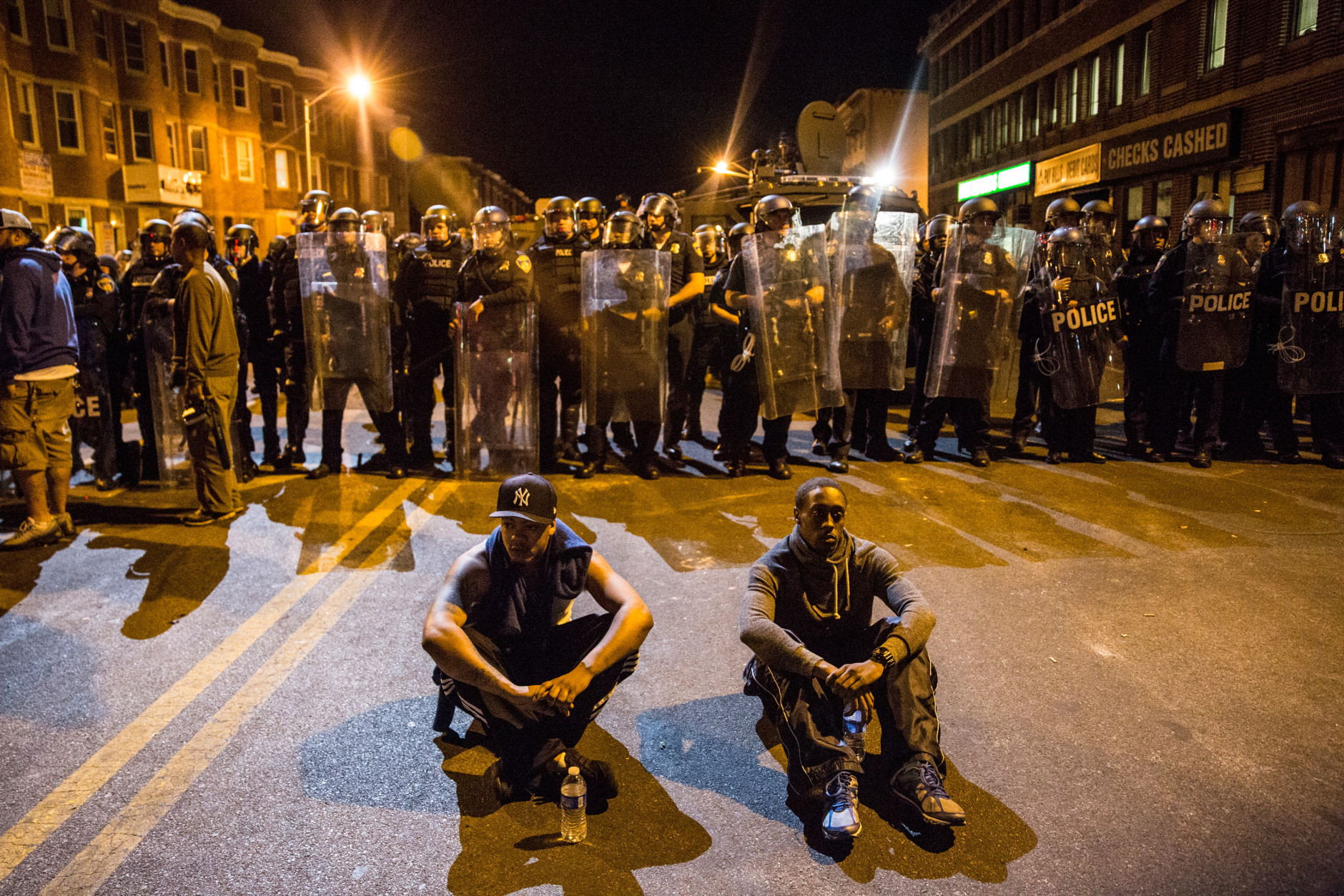 BALTIMORE, MD - APRIL 28:  Two protesters sit on the ground in front of riot police minutes before a mandatory, city-wide curfew of 10 p.m. near the CVS pharmacy that was set on fire yesterday during rioting after the funeral of Freddie Gray, on April 28, 2015 in Baltimore, Maryland. Gray, 25, was arrested for possessing a switch blade knife April 12 outside the Gilmor Houses housing project on Baltimore's west side. According to his attorney, Gray died a week later in the hospital from a severe spinal cord injury he received while in police custody.  (Photo by Andrew Burton/Getty Images)