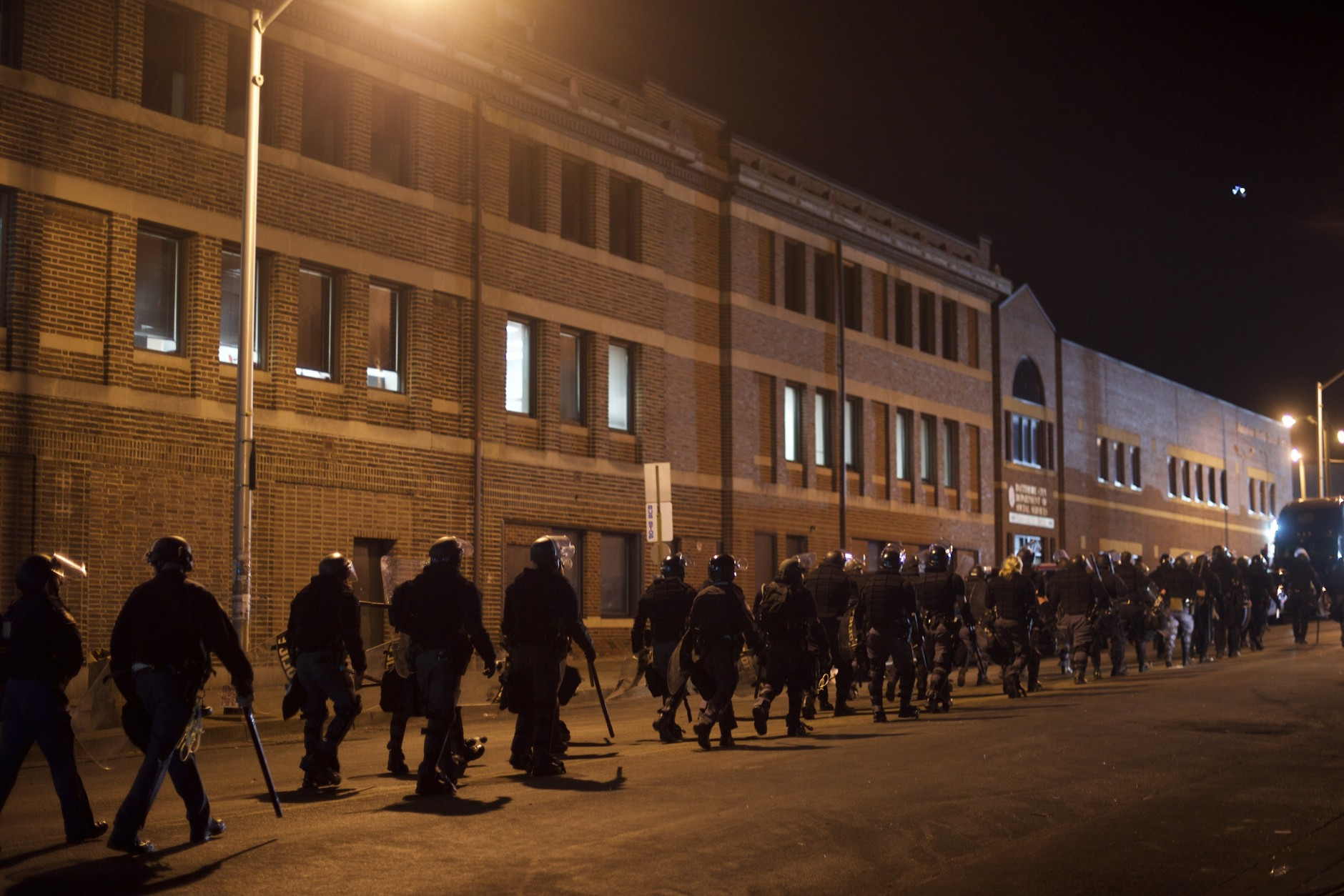 Riot police depart after forming a barricade and dispensing tear gas near the burned out CVS pharmacy the night after citywide riots over the death of Freddie Gray on April 28, 2015 in Baltimore, Maryland. Freddie Gray, 25, was arrested for possessing a switch blade knife April 12 outside the Gilmor Houses housing project on Baltimore's west side. According to his attorney, Gray died a week later in the hospital from a severe spinal cord injury he received while in police custody. (Photo by Mark Makela/Getty Images)
