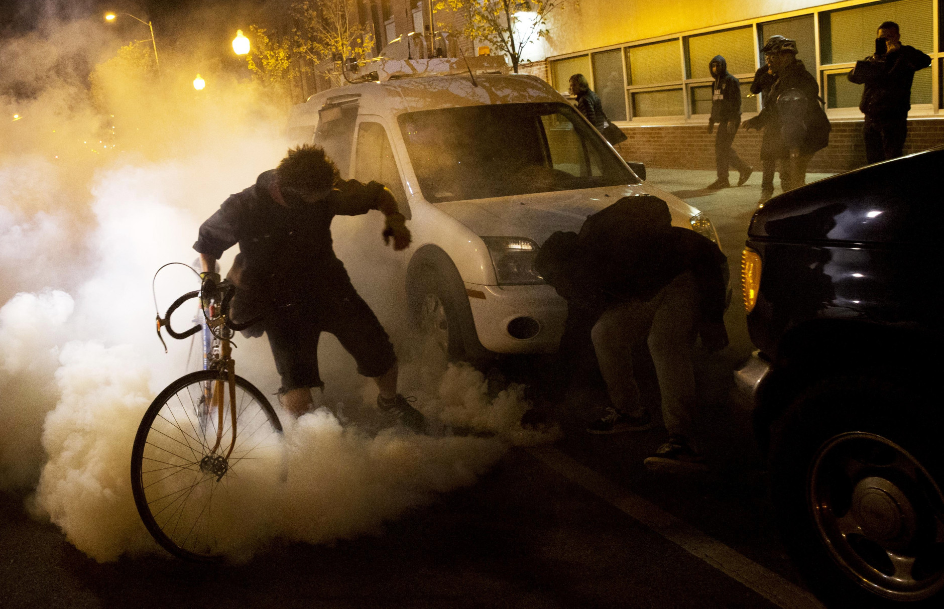 Protesters attempt to throw a tear gas canister back toward riot police after a 10 p.m. curfew went into effect in the wake of Monday's riots following the funeral for Freddie Gray, Tuesday, April 28, 2015, in Baltimore. (AP Photo/David Goldman)