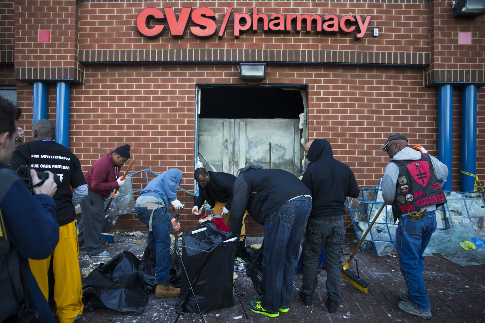 Maryland state troopers stand guard as residents clean up, Tuesday, April 28, 2015, after an evening of riots following the funeral of Freddie Gray on Monday, in Baltimore. (AP Photo/Evan Vucci)