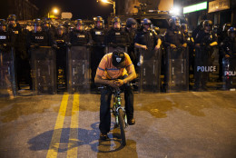 A man sits on a bicycle in front of a line of police officers in riot gear as part of a community effort to disperse the crowd ahead of a 10 p.m. curfew in the wake of Monday's riots following the funeral for Freddie Gray, Tuesday, April 28, 2015, in Baltimore. (AP Photo/David Goldman)