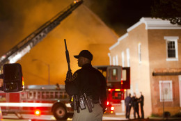 An officer stands near a blaze, Monday, April 27, 2015, after rioters plunged part of Baltimore into chaos, torching a pharmacy, setting police cars ablaze and throwing bricks at officers. (AP Photo/Matt Rourke)