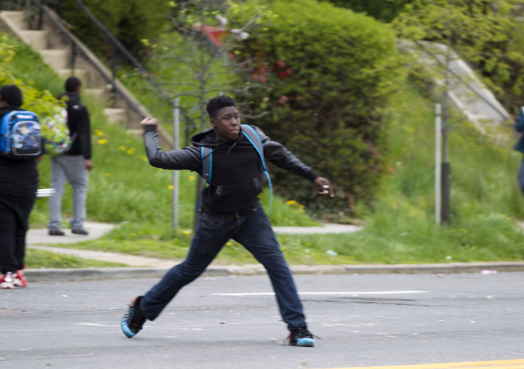 A demonstrator throws a rock at the police after the funeral of Freddie Gray on Monday, April 27, 2015, at New Shiloh Baptist Church in Baltimore. Gray died from spinal injuries about a week after he was arrested and transported in a Baltimore Police Department van. (AP Photo/Jose Luis Magana)