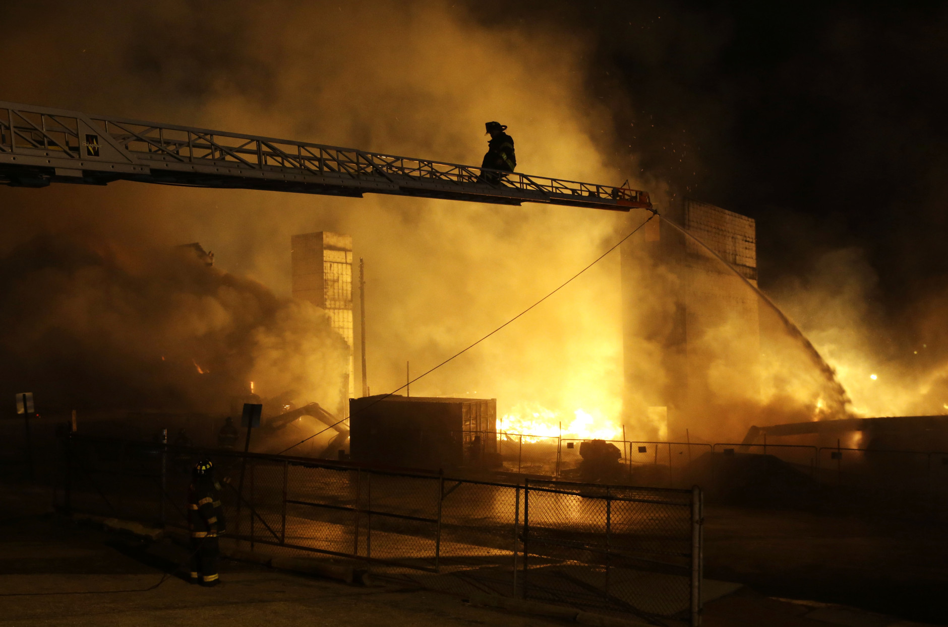 Firefighters battle a blaze, Monday, April 27, 2015, after rioters plunged part of Baltimore into chaos, torching a pharmacy, setting police cars ablaze and throwing bricks at officers.  (AP Photo/Patrick Semansky)