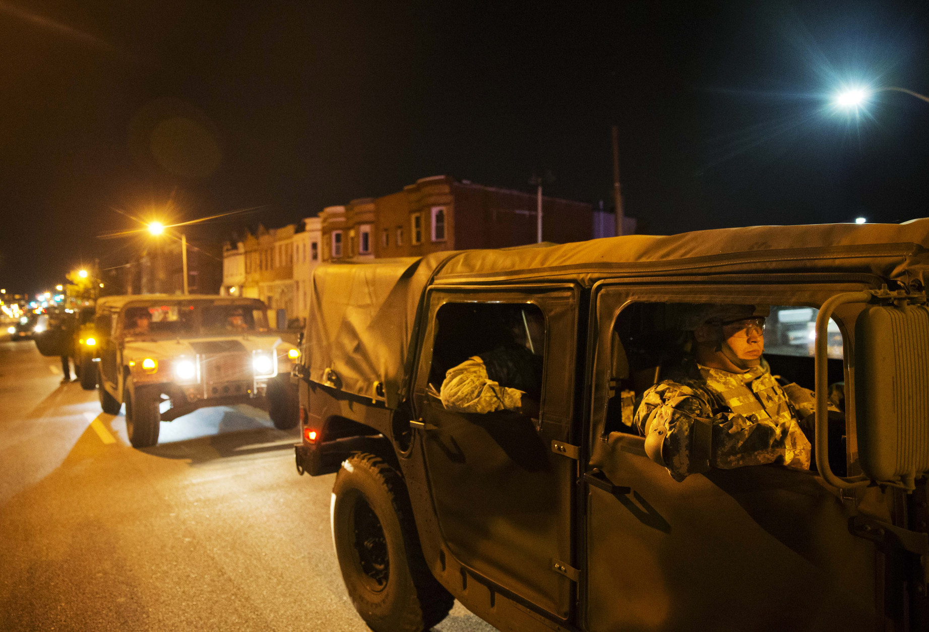 Members of the National Guard pass through the area where Monday's riots occurred following the funeral for Freddie Gray, after a 10 p.m. curfew went into effect, Tuesday, April 28, 2015, in Baltimore. (AP Photo/David Goldman)