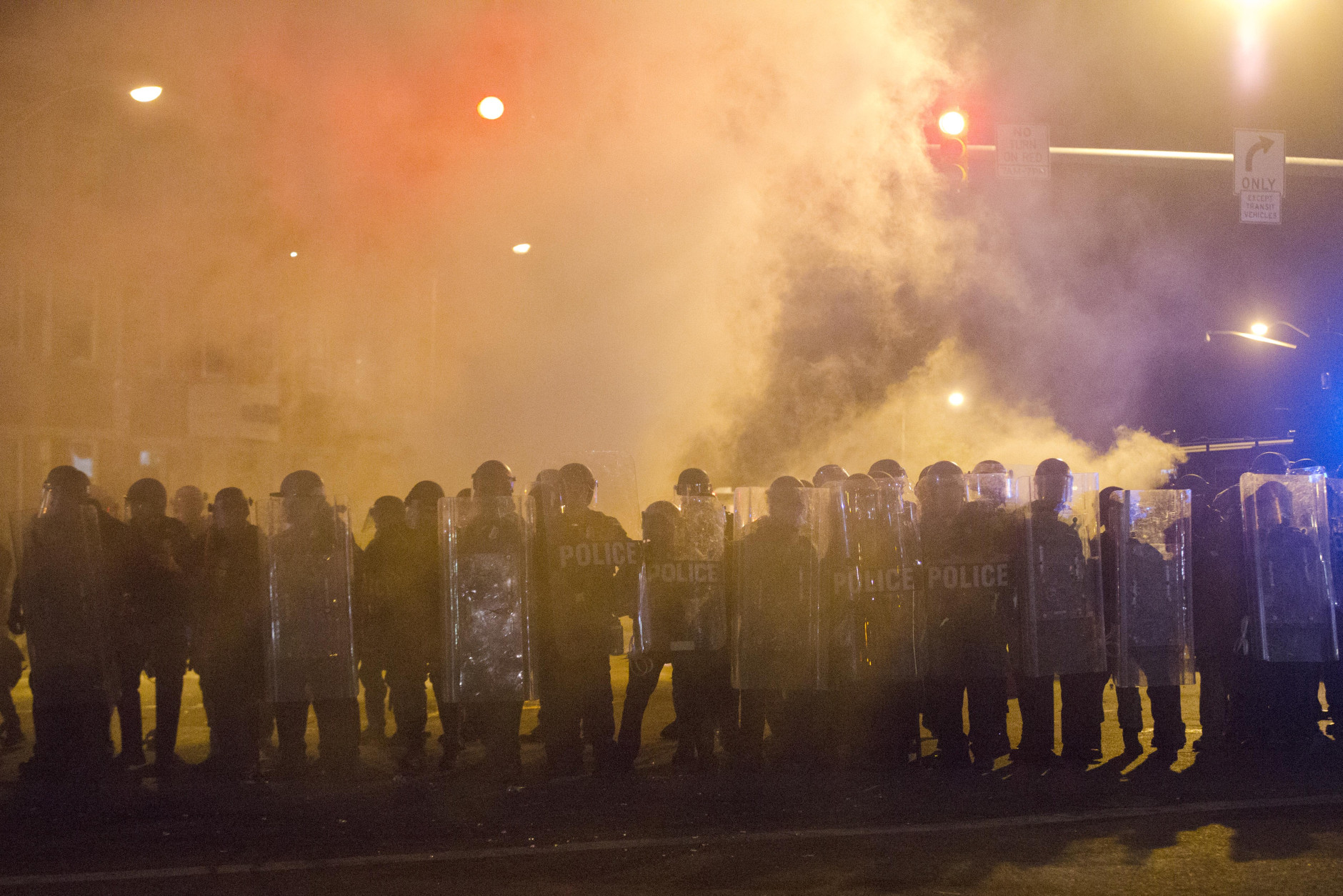 Police enforce a 10 p.m. curfew that went into effect in the wake of Monday's riots following the funeral for Freddie Gray, Tuesday, April 28, 2015, in Baltimore. (AP Photo/Matt Rourke)