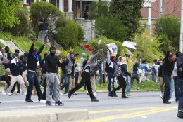 Demonstrators throw rocks to the police, after the funeral of Freddie Gray, Monday, April 27, 2015, at New Shiloh Baptist Church in Baltimore. Gray died from spinal injuries about a week after he was arrested and transported in a Baltimore Police Department van.  (AP Photo/Jose Luis Magana)
