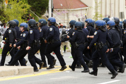 Baltimore police officers push back demonstrators who are throwing rocks at the police, after the funeral of Freddie Gray, Monday, April 27, 2015, at New Shiloh Baptist Church in Baltimore. Gray died from spinal injuries about a week after he was arrested and transported in a Baltimore Police Department van.  (AP Photo/Jose Luis Magana)