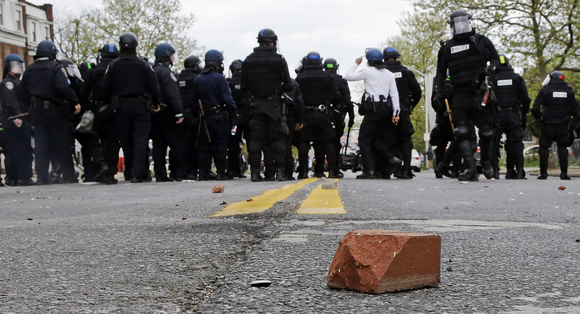 A brick sits on a street as police standby, Monday, April 27, 2015, during a skirmish with demonstrators after the funeral of Freddie Gray in Baltimore. Gray died from spinal injuries about a week after he was arrested and transported in a Baltimore Police Department van. (AP Photo/Patrick Semansky)
