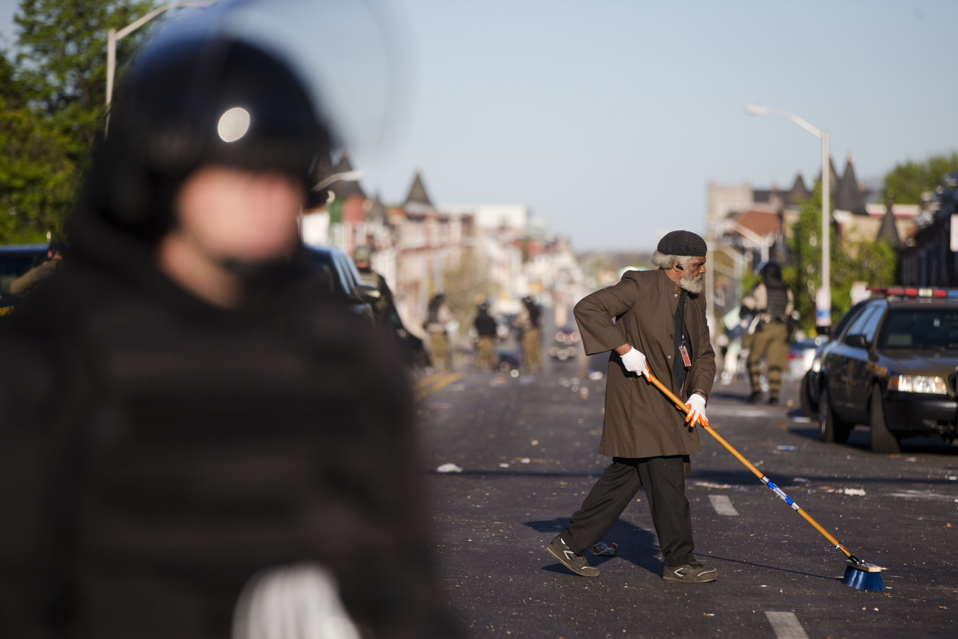 Residents clean streets as law enforcement officers stand guard, Tuesday, April 28, 2015, in Baltimore, in the aftermath of rioting following Monday's funeral of Freddie Gray, who died in police custody. (AP Photo/Matt Rourke)