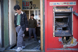 Jason Park, left, and his friend business owner Sung Kang, second left, leave his damaged store, Tuesday, April 28, 2015, in the aftermath of rioting following Monday's funeral for Freddie Gray, who died in police custody. The violence that started in West Baltimore on Monday afternoon had spread to East Baltimore and neighborhoods close to downtown and near Camden Yards.  (AP Photo/Matt Rourke)